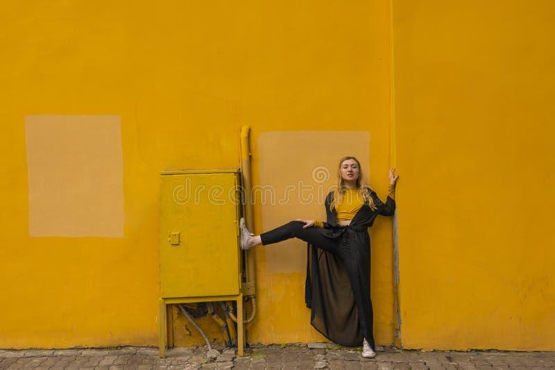 Millennial stilfull ung blond modeflickastående på en gul stadsbakgrund nära väggen arkivbilder