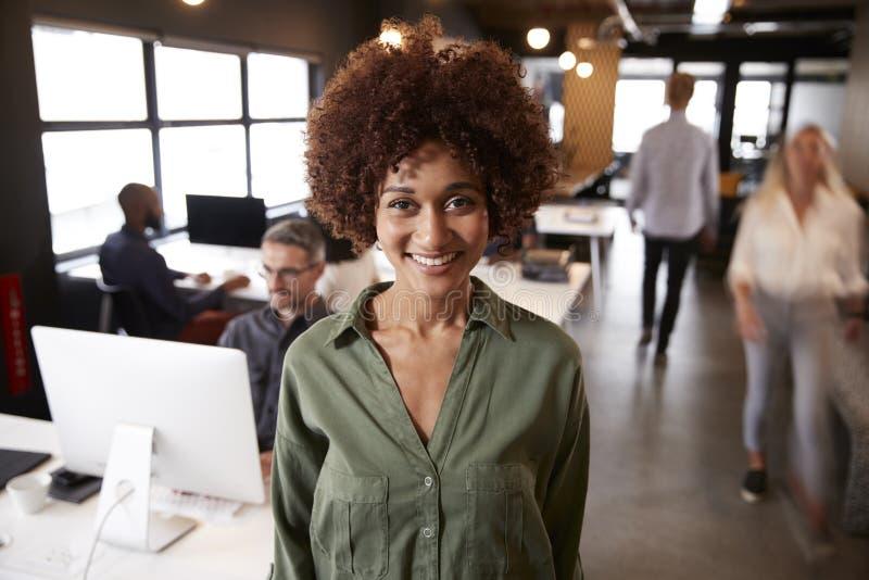 Millennial svart kvinnligt idérikt anseende i ett upptaget tillfälligt kontor som ler till kameran arkivbilder