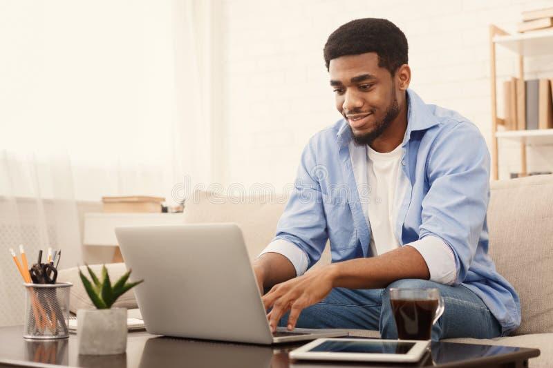 Millennial svart man som arbetar p? b?rbara datorn i inrikesdepartementet royaltyfria foton