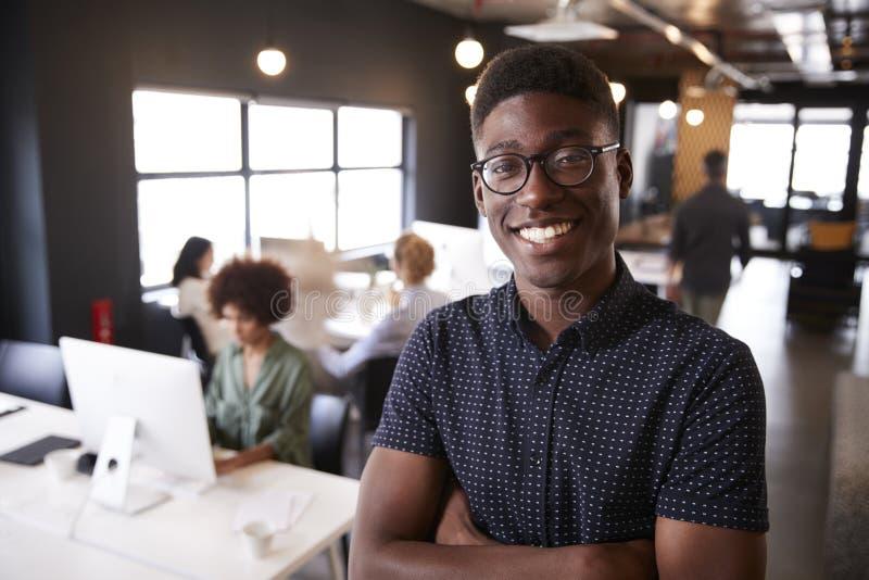 Millennial svart manligt idérikt anseende i ett upptaget tillfälligt kontor som ler till kameran royaltyfria foton