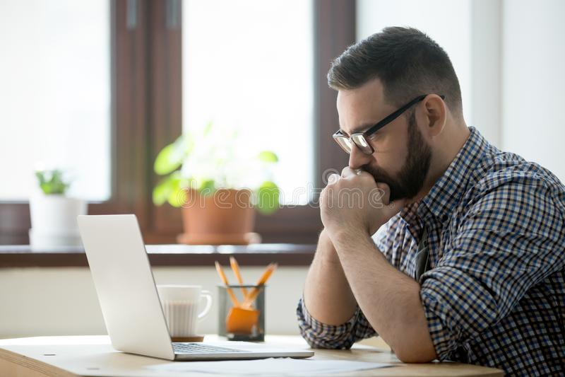 Millennial tillfällig affärsman som in tänker och ser bärbara datorn arkivfoto