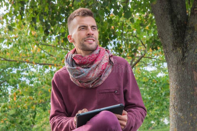 Millennial używa pastylka komputer osobisty w parku z zielonymi drzewami obrazy royalty free