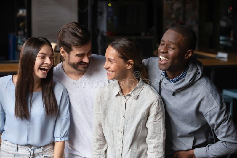 Millennial vänner för olik etnicitet som har gyckel som inomhus står arkivfoto