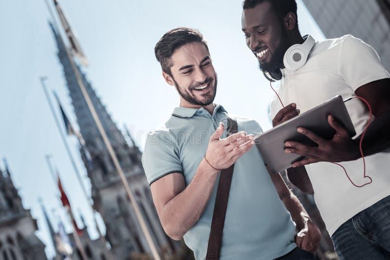 Millennial vänner som ler, medan se touchpaden arkivbilder