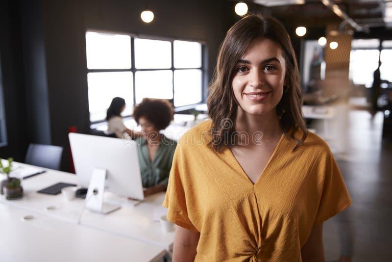 Millennial vitt kvinnligt idérikt anseende i ett upptaget tillfälligt kontor som ler till kameran royaltyfri bild