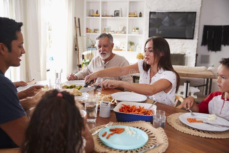 Millennial vrouw die haar verwanten dienen bij een maaltijd van de drie generatie Spaanse familie stock fotografie