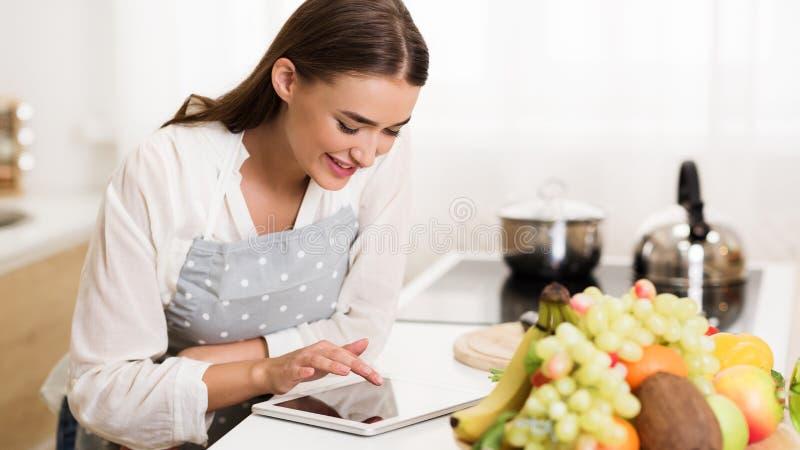Millennial vrouw die recept op tablet zoeken, die diner koken stock afbeeldingen