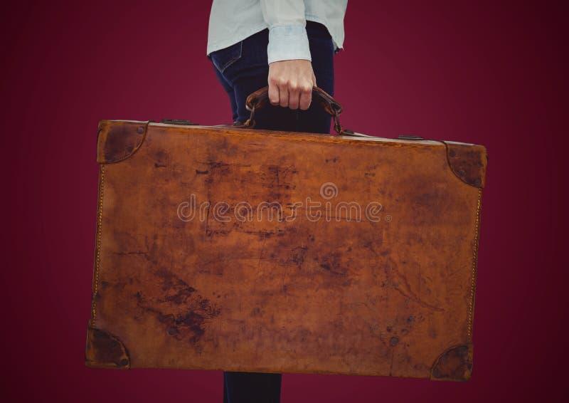 Millennial vrouwen lager lichaam met koffer tegen kastanjebruine achtergrond stock afbeelding