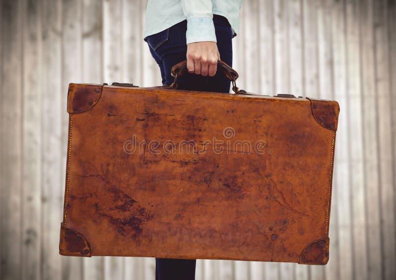 Millennial vrouwen lager lichaam met koffer tegen onscherp houten paneel royalty-vrije stock afbeelding