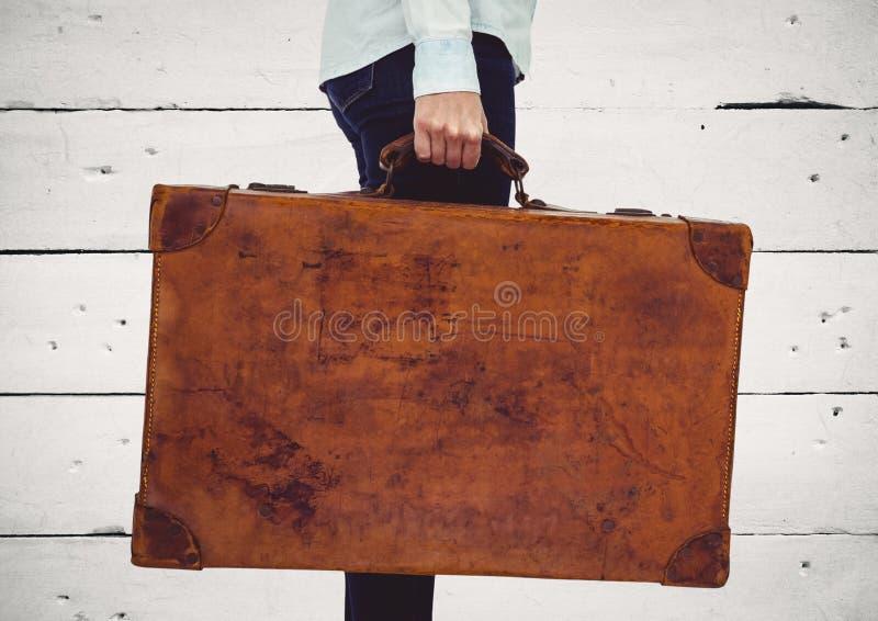 Millennial vrouwen lager lichaam met koffer tegen wit houten paneel stock foto's