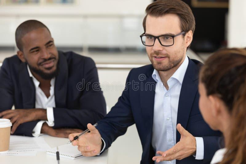 Millennial werkgever die collectieve multiraciale teamvergadering leiden bij bestuurskamer stock afbeelding