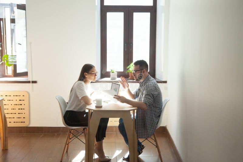 Millennial werknemers die commerciële vergadering hebben en over w debatteren royalty-vrije stock foto