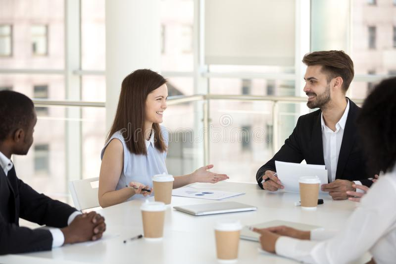 Millennial werknemers die het onderhandelen glimlachen bij bureaubriefing stock foto's