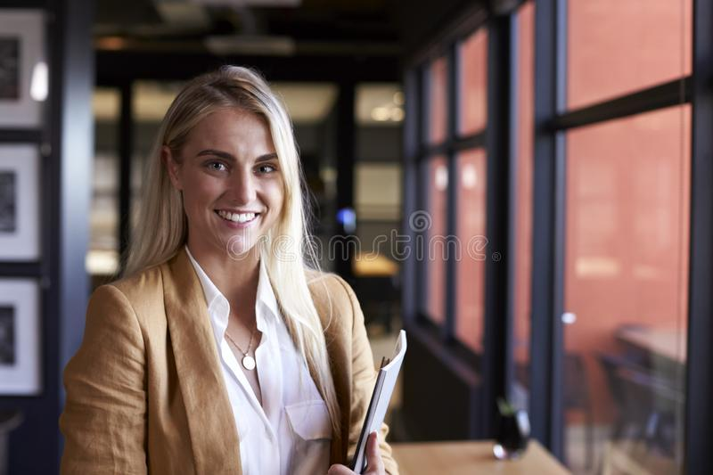 Millennial white blonde businesswoman smiling to camera by the window in an office, close up royalty free stock photo