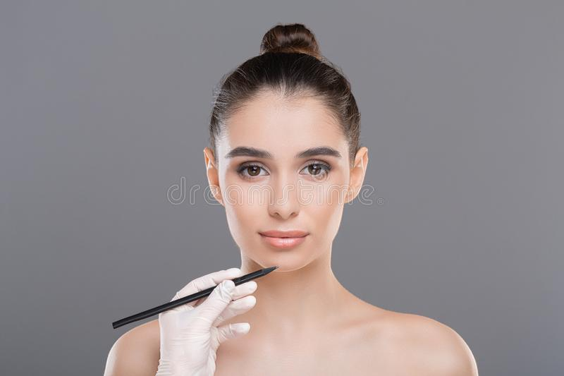 Millennial woman and doctor`s hand with pencil. Plastic surgery. Millennial woman and doctor`s hand with pencil, gray studio background royalty free stock photography