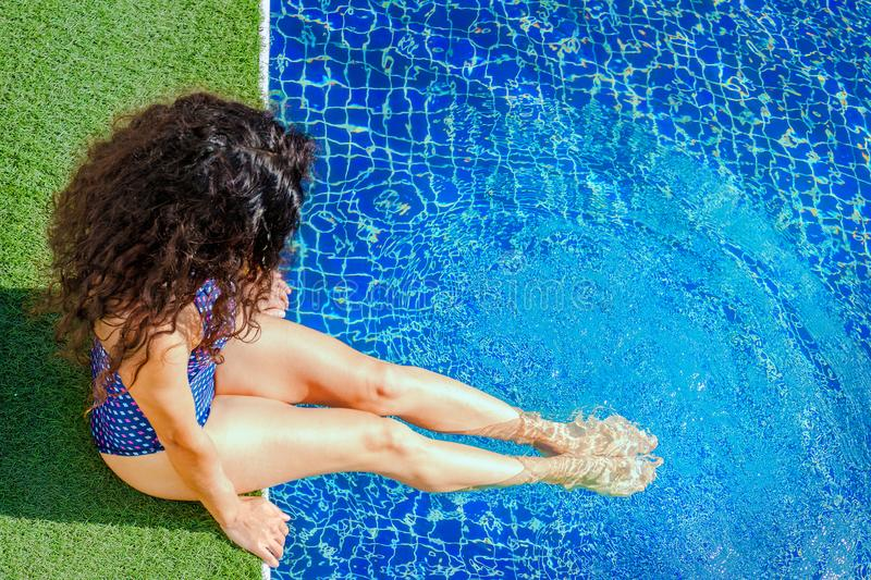 Millennial woman relaxing by the pool with legs dipped in water. Health care - Vitamin D is produced in the sun. stock photos