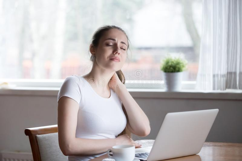Woman have neck pain working on laptop. Millennial woman sitting in kitchen at table touch massage neck. Exhausted tired girl suffering from neck pain ache after stock photos