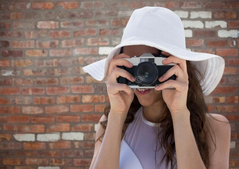 Millennial woman in summer hat with camera against red brick wall. Digital composite of Millennial woman in summer hat with camera against red brick wall royalty free stock photos