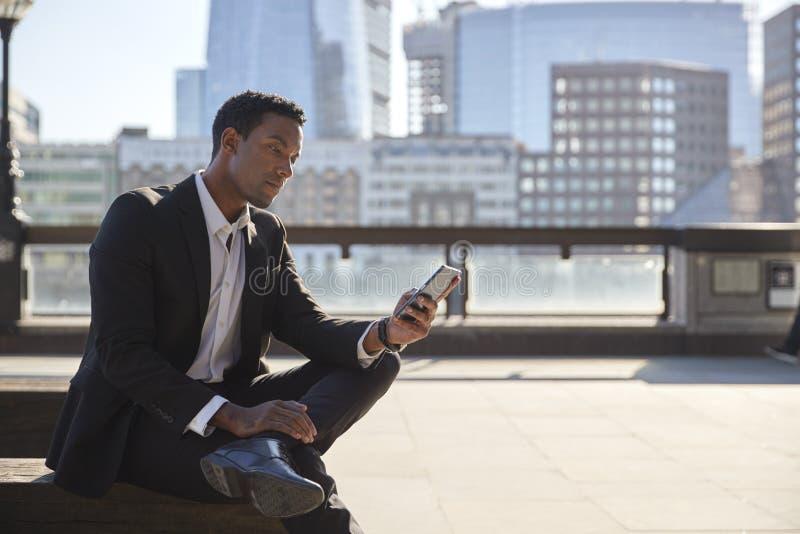 Millennial zakenman die zwart kostuum en witte overhemdszitting op de dijk dragen die van Riviertheems smartphone gebruiken, slui stock afbeelding
