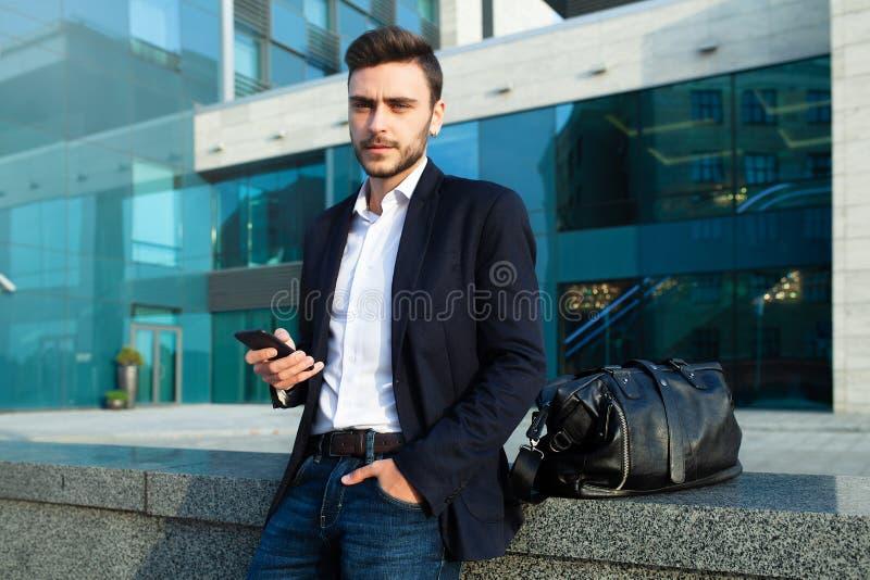 Millennial zakenman met een mobiele telefoon in zijn handen Jonge succesvolle bedrijfs modieuze mens met een zwarte leerzak stock afbeelding