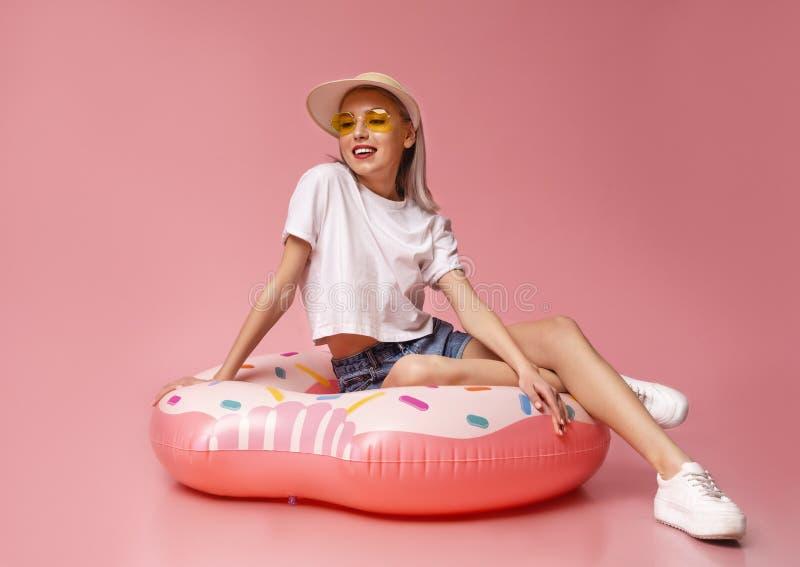 Millennial Zitting van de Blondevrouw op Doughnut Opblaasbare Ring stock fotografie