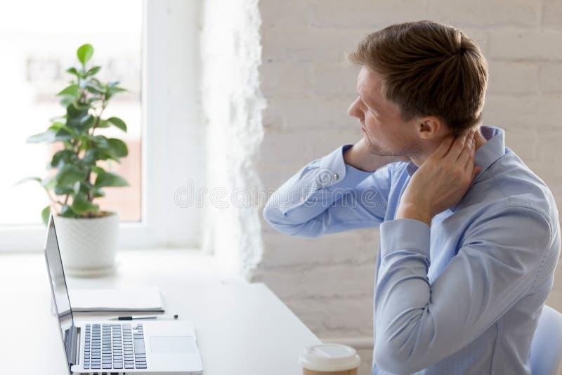 Millennial zmęczony mężczyzna ma szyja ból zdjęcie stock