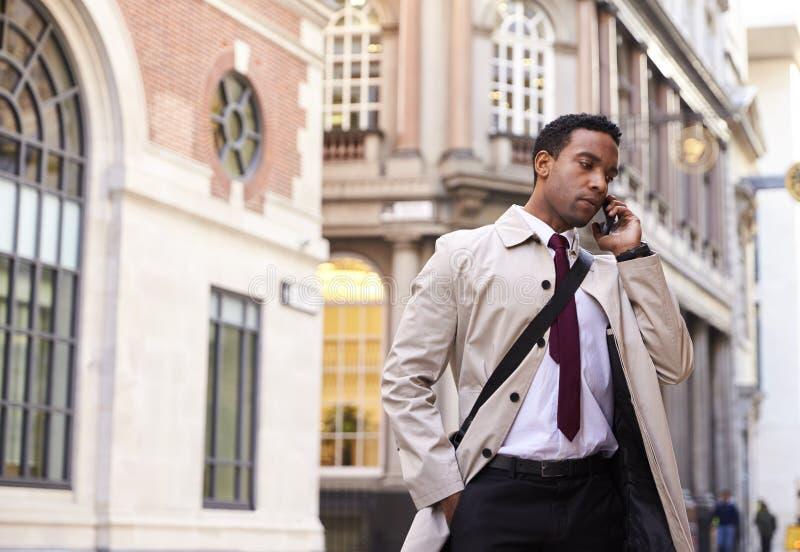 Millennial zwarte zakenman die zich op een straat in Londen bevinden die op zijn telefoon, lage hoek spreken stock foto