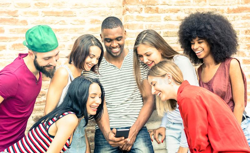 Millennials bästa vän som använder den smarta telefonen på stadshögskolaträdgården - ungdomarsom missbrukas av den mobila smartph royaltyfria bilder