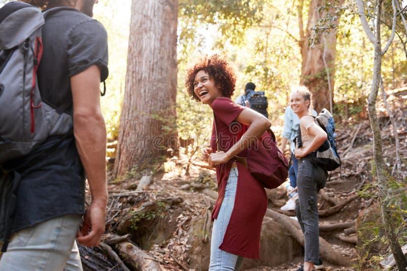 Millennials che fa un'escursione su una traccia della foresta che gira intorno per esaminare indietro gli amici, tre lunghezze qu fotografia stock