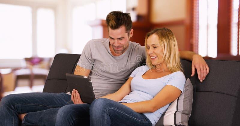 Millennials che guarda i video divertenti sulla compressa a casa che si siede insieme su uno strato fotografia stock