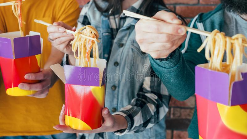 Unhealthy takeout food hands chinese noodles boxes. Millennials eating habit. Takeout food. Unhealthy nutrition. Hands with Chinese noodles boxes closeup royalty free stock photography