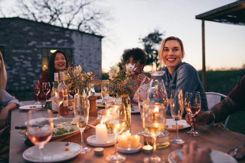 Millennials enjoying dinner in outdoor restaurant. Group of friends enjoying outdoor party in garden restaurant . Millennials enjoying dinner outdoors stock photos