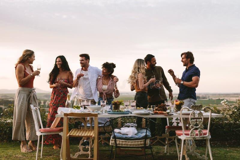 Millennials enjoying dinner party outdoors stock image