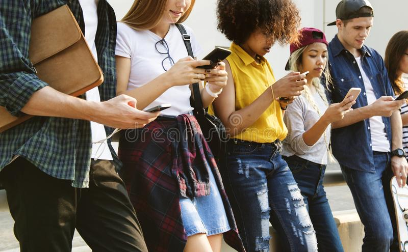 Millennials genom att använda mångfald för smartphones utomhus arkivfoto