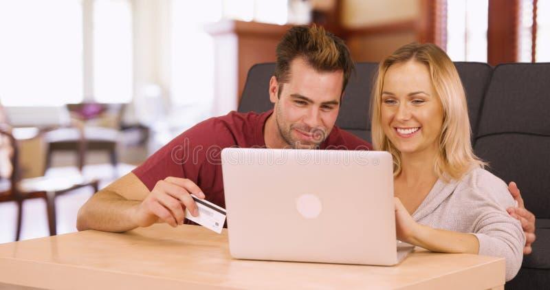 Millennials het online thuis winkelen samen op laptop stock afbeelding