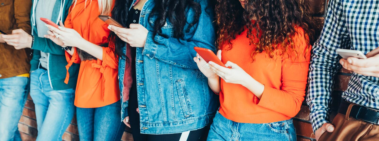 Millennials style casual denim outfit smartphones. Millennials style. Young people in trendy denim outfits standing with smartphones, reading messages, posts in royalty free stock photos