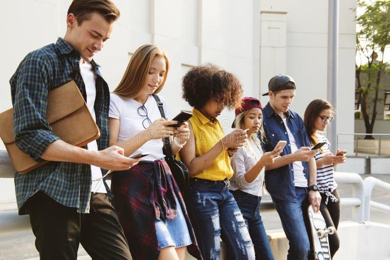 Millennials using smartphones outdoors together stock photo