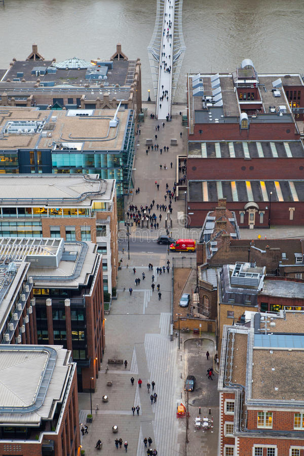 Millennium foot bridge over the River Thames and office people walking through the streets royalty free stock photography