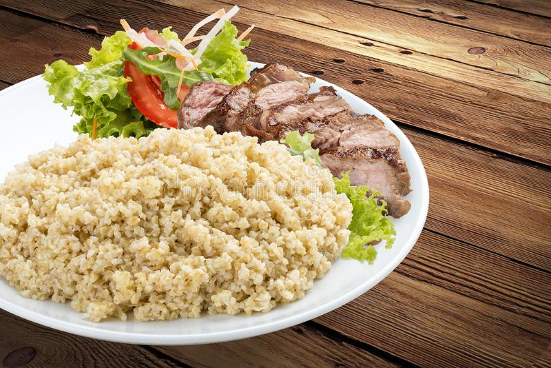 Millet porridge with pork grilled. On a wooden background royalty free stock image