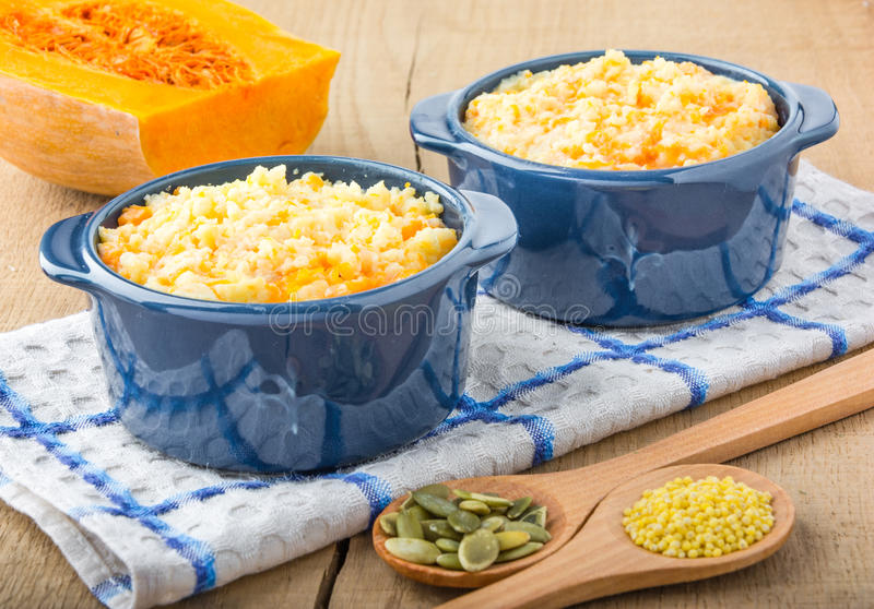 Millet porridge with pumpkin. In blue bowl on a kitchen towel, pumpkin seeds and millet in a wooden spoons and pumpkin on a wooden table royalty free stock images