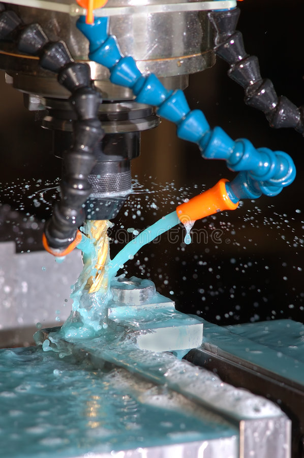 Milling. Machine is making part while coolant is spraying stock images