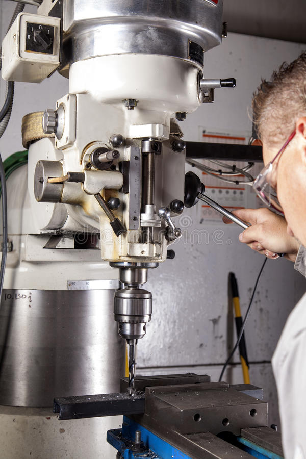 Milling Machine. A worker using a milling machine to drill a hole in a piece of metal royalty free stock images