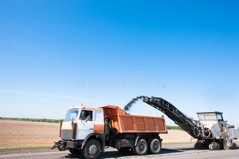 Milling machine removing crushed aphalt into dump truck royalty free stock images