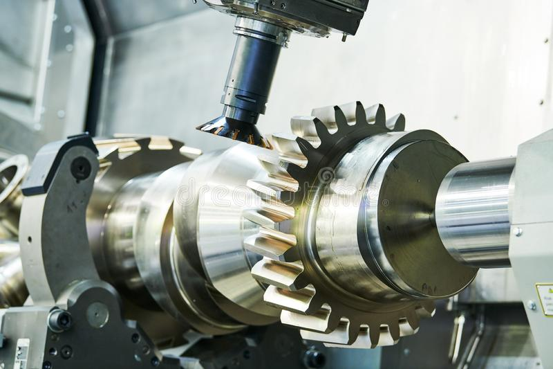 Cogwheel on shaft milling process. Industrial CNC metal machining by vertical mill. Milling metalworking process. Industrial CNC machining of tooth gear on shaft stock photos