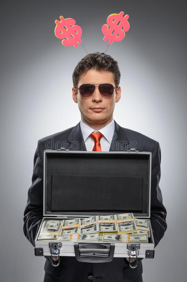Millionaire. Confident man in formal wear holding a suitcase full of money while standing isolated on gray stock photography