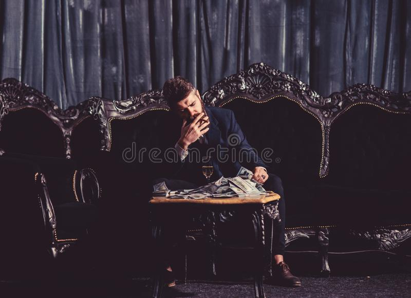 Millionaire in elegant suit smokes and drinks on luxurious sofa. royalty free stock image