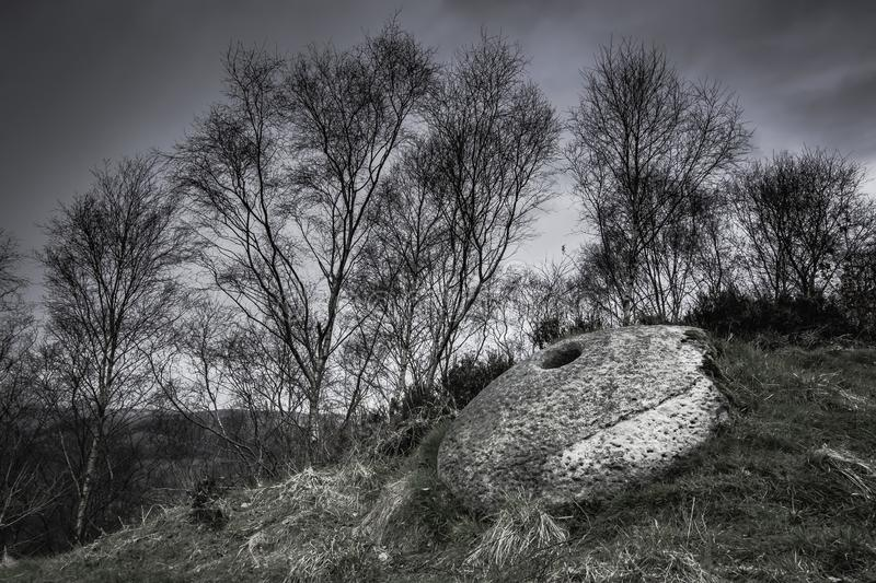 Millstone in Derbyshire, UK. Remains of Stone Age culture.Ancient millstone used to grind barley grains and produce flour in past.Peak District, Derbyshire, UK stock photo