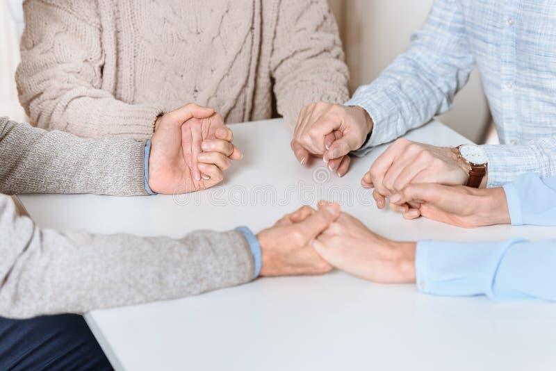 mily坐在桌上和握手彼此的朋友的播种的图象,当祈祷时 免版税库存图片