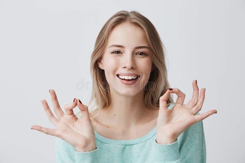 Mim fazer do ` m grande Fêmea loura nova feliz contente na camiseta azul que sorri amplamente e que faz o gesto aprovado com amba foto de stock