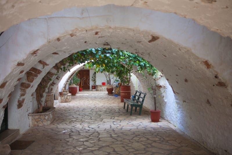 Mim o monastério de Paleokastritsa - arcada agradável com potenciômetros de flor imagens de stock royalty free